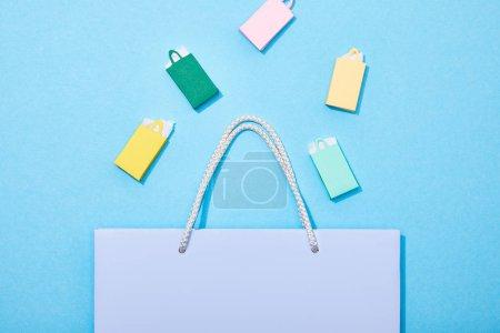 Photo pour Vue du dessus des sacs en papier colorés tombant dans le sac à provisions violet sur bleu - image libre de droit