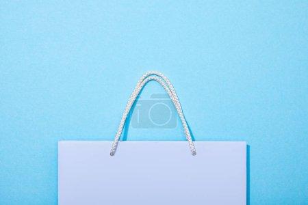 Photo pour Vue du dessus du sac à provisions violet sur bleu - image libre de droit