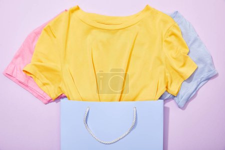 Photo for Top view of colorful t-shirts in shopping bag on violet - Royalty Free Image