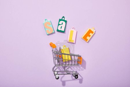 top view of colorful toy bags with sale lettering near shopping cart with yellow paper bag on violet