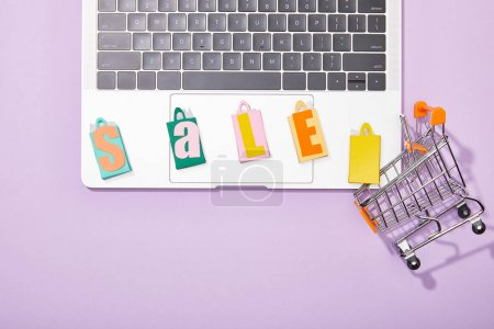 Foto de Top view of colorful shopping bags with sale lettering on laptop near small toy cart on violet - Imagen libre de derechos