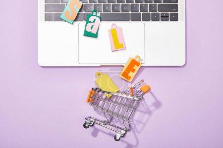 vue du haut des sacs de jouets colorés avec lettrage de vente sur ordinateur portable tombant dans le panier de jouets sur violet