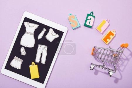 Foto de Top view of paper cut of clothes on digital tablet near shopping bags with sale lettering falling into toy cart on violet - Imagen libre de derechos