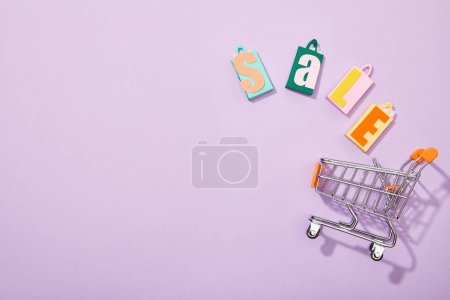 Photo for Top view of colorful shopping bags with sale inscription falling into toy cart on violet - Royalty Free Image