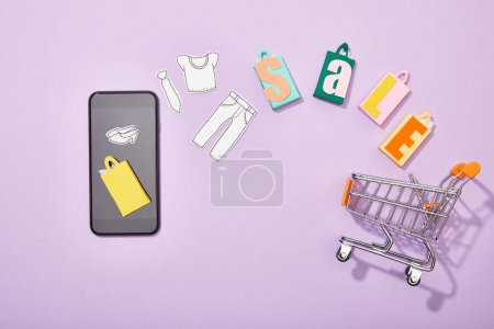 top view of smartphone near shopping bags with sale lettering and paper cut of clothes falling into toy cart on violet