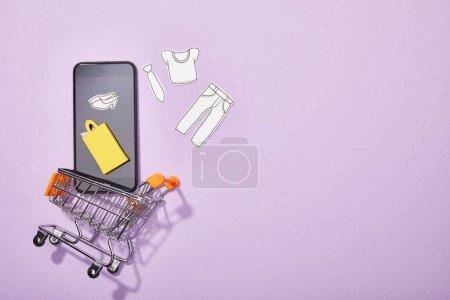 Foto de Vista superior del teléfono inteligente con el corte de papel de la ropa y la bolsa de papel amarillo cayendo en el carrito de juguete en violeta - Imagen libre de derechos