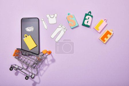 top view of smartphone with paper cut of clothes and yellow paper bag falling into toy cart near colorful shopping bags with sale lettering on violet