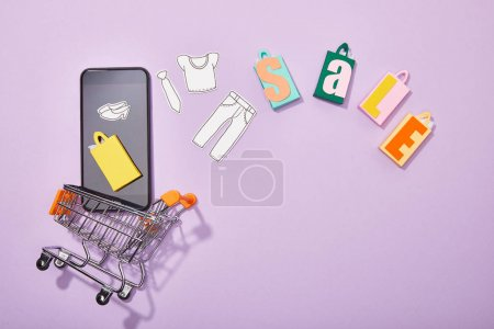 Photo for Top view of smartphone with paper cut of clothes and yellow paper bag falling into toy cart near colorful shopping bags with sale lettering on violet - Royalty Free Image