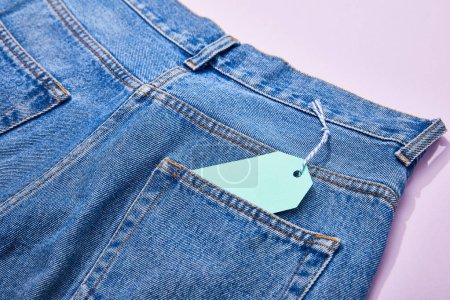 Photo pour Fermer la vue vers le haut de l'étiquette de vente de papier turquoise sur la corde sur des jeans sur le violet - image libre de droit