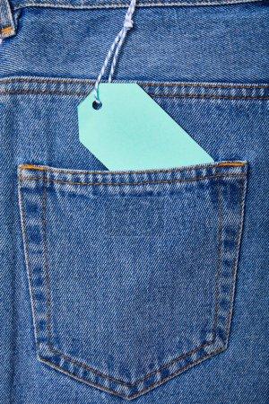 Photo pour Vue rapprochée du papier turquoise étiquette de vente sur corde sur jeans - image libre de droit