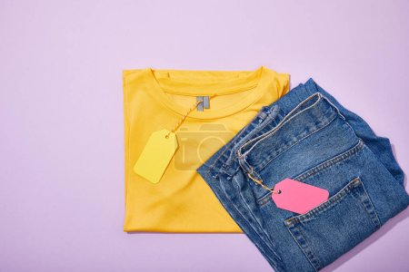 Photo for Top view of colorful sale tags on t-shirt and jeans on violet - Royalty Free Image