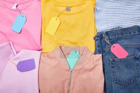 Photo pour Pose plate avec étiquettes de vente de papier sur différents vêtements colorés - image libre de droit