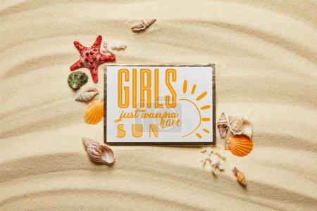 Photo pour Vue du dessus de la plaque avec les filles veulent juste avoir lettrage soleil près des coquillages, étoiles de mer et coraux blancs sur la plage de sable fin - image libre de droit