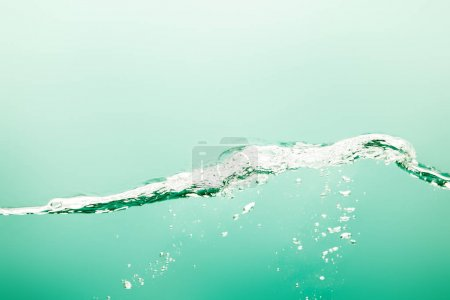 transparent pure water with splash and bubbles on green background