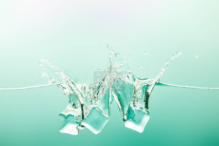 transparent pure water with splash and ice cubes on green background