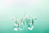 """Постер, картина, фотообои """"прозрачная чистая вода с брызгами и кубиками льда на зеленом фоне"""""""