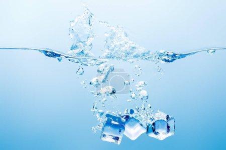 Photo pour L'eau pure avec l'éclaboussure, les bulles et les glaçons sur le fond bleu - image libre de droit