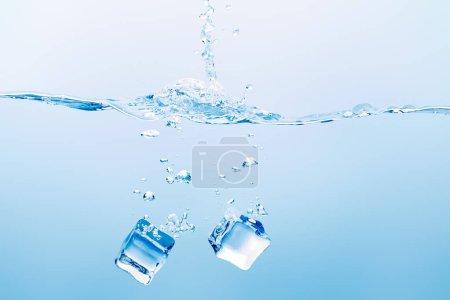 agua pura transparente con salpicaduras y cubitos de hielo cuadrados sobre fondo azul