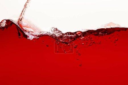 liquide brillant rouge coulant avec éclaboussures et bulles isolées sur blanc
