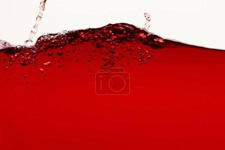 Photo pour Liquide lumineux rouge avec éclaboussure isolé sur blanc - image libre de droit