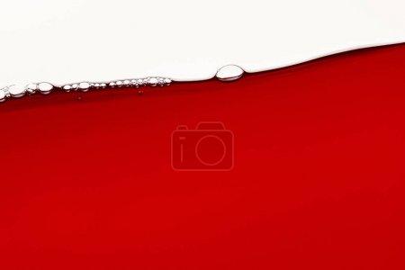 Photo pour Rouge liquide brillant avec des bulles sur la surface isolé sur blanc - image libre de droit