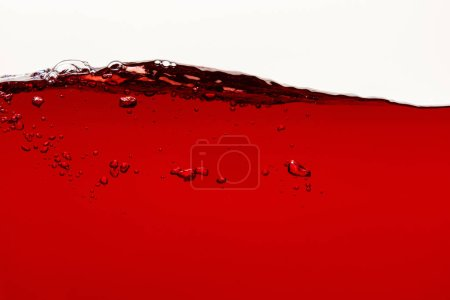 Photo for Wavy red bright liquid with bubbles isolated on white - Royalty Free Image