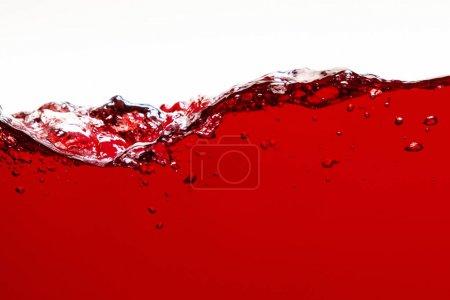 Photo pour Liquide lumineux rouge avec des éclaboussures et des bulles d'isolement sur le blanc - image libre de droit
