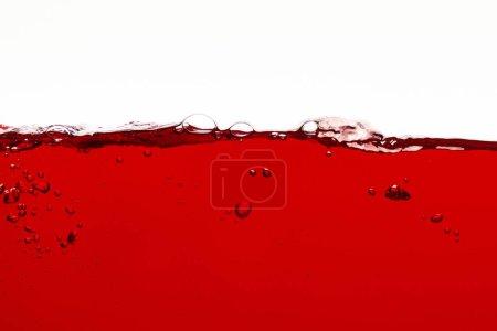 Photo pour Liquide coloré rouge avec des bulles sur la surface d'isolement sur le blanc - image libre de droit