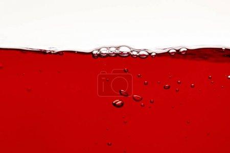 Photo pour Liquide lumineux rouge avec des bulles sur la surface isolée sur le blanc - image libre de droit
