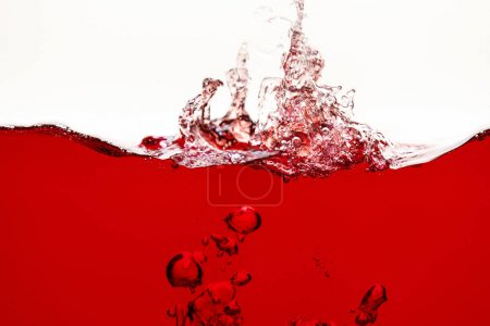 Photo for Red bright liquid with splash and underwater bubbles isolated on white - Royalty Free Image