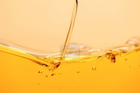 yellow bright liquid stream with splash and bubbles isolated on yellow