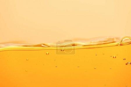 Photo pour Liquide brillant jaune ondulé avec éclaboussures et bulles isolées sur jaune - image libre de droit