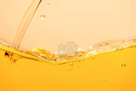 Photo for Pouring yellow bright liquid with splash and bubbles isolated on yellow - Royalty Free Image