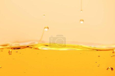 Photo pour Liquide brillant jaune avec gouttes et bulles isolées sur jaune - image libre de droit