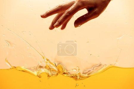 Photo pour Vue recadrée de la main et jaune éclaboussures brillantes liquide isolé sur jaune - image libre de droit