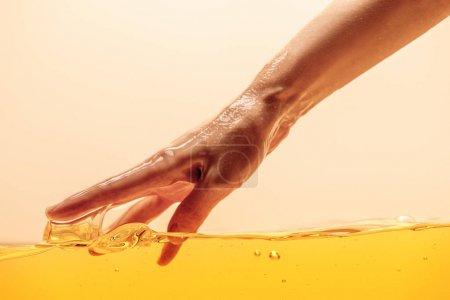 Photo pour Vue partielle de la main touchant jaune liquide brillant isolé sur jaune - image libre de droit