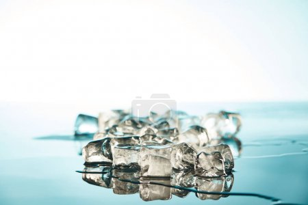 Photo for Stack of transparent melting ice cubes on emerald and white background - Royalty Free Image