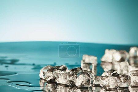 Foto de Cubos de hielo de fusión transparente sobre fondo esmeralda y blanco - Imagen libre de derechos