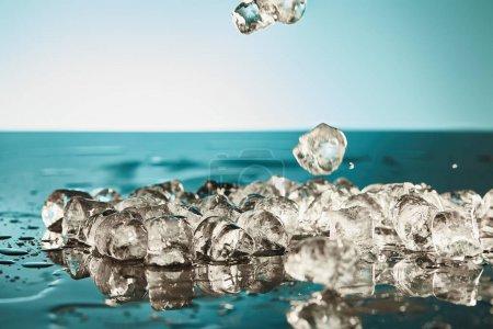 Photo for Melting ice cubes on emerald and white background - Royalty Free Image
