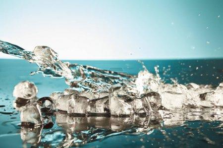 Photo pour Glaces transparentes fondantes avec de l'eau éclaboussures sur fond émeraude et blanc - image libre de droit