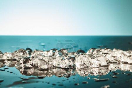 Foto de Cubos de hielo defusión fresco sobre fondo esmeralda y blanco - Imagen libre de derechos