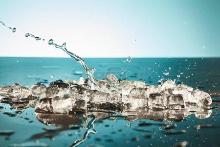 Photo pour Glaçons fondus transparents et éclaboussures d'eau sur fond émeraude et blanc - image libre de droit