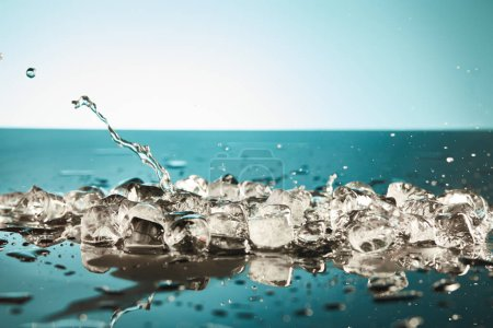 Foto de Melting ice cubes and water splash on emerald and white background - Imagen libre de derechos