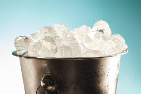 Foto de Cubitos de hielo fresco en cubo de metal sobre fondo esmeralda y blanco - Imagen libre de derechos