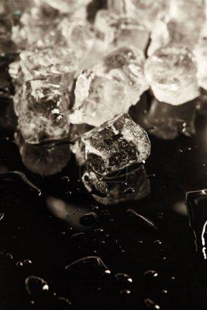 Foto de Stack of transparent cool ice cubes on black background with drops - Imagen libre de derechos