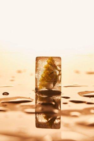 transparenter Eiswürfel mit gefrorener Blume auf gelb beleuchtetem Hintergrund