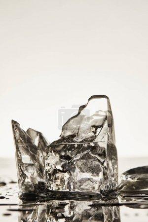 Photo pour Glaçons fondus transparents avec gouttes et flaques sur fond blanc - image libre de droit