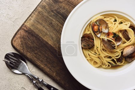close up view of delicious pasta with mollusks on wooden cutting board on white background