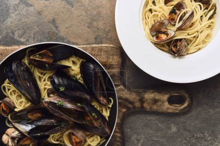 Photo for Top view of delicious pasta with mollusks and mussels on weathered grey background - Royalty Free Image