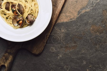 Photo for Top view of delicious pasta with mollusks on wooden aged cutting board on weathered background with copy space - Royalty Free Image